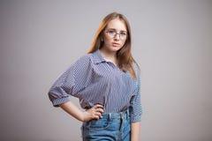 Стекла уверенно молодой девушки студента нося и смотреть камеру Успешная женщина Redhead в striped блузке и сини стоковая фотография rf