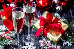 Стекла шампанского и орнаментов рождества на темной деревянной задней части Стоковые Фото