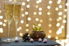 2 стекла шампанского и шоколадов на предпосылке праздничных гирлянд, белых падениях снега Стоковое Изображение RF
