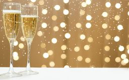 2 стекла шампанского против праздничных гирлянд, белый снег падают Стоковые Изображения