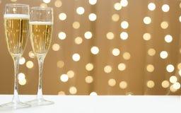 2 стекла шампанского против праздничных гирлянд Стоковое Фото