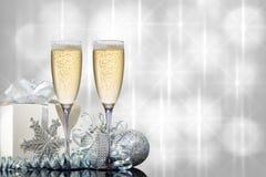 2 стекла шампанского с подарком и игрушками рождества на красивой предпосылке стоковое изображение