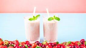 2 стекла smoothies сделанных от молока, клубник, банана, вишен, украшенных с мятой на яркой розовой сини стоковые фото