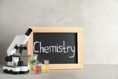 Стеклоизделие, микроскоп и доска лаборатории со словом ХИМИЕЙ на таблице против серой предпосылки стоковые изображения rf