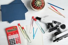 Стеклоизделие, микроскоп и школьные принадлежности лаборатории на деревянной предпосылке стоковые фотографии rf