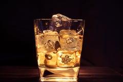 Стекло вискиа с кубами льда на темном tabl предпосылки и древесины Стоковые Фото