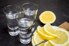 Стекло водочки И лимон отрезая на плите Место для вашего текста Стоковое Изображение RF