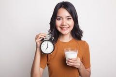 Стекло здоровой азиатской женщины выпивая часов владением молока Стоковое Изображение RF