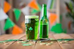 Стекло зеленого пива с shamrock и подковой Стоковые Фото