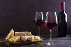 Стекло и бутылка вина с сыром, виноградинами, и гайками на черном деревянном столе Вино и еда стоковые изображения rf