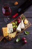 Стекло и бутылка вина с сыром, виноградинами, и гайками на черном деревянном столе Вино и еда стоковое фото
