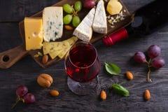 Стекло и бутылка вина с сыром, виноградинами, и гайками на черном деревянном столе Вино и еда стоковые фото