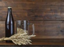 Стекло и бутылка пива, ушей ячменя на деревянной предпосылке A стоковые изображения rf