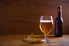 Стекло и бутылка пива, ушей ячменя на деревянной предпосылке aleppo стоковые фото