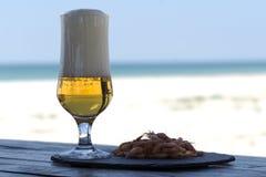 Стекло и креветки пива на каменной плите в таблице тени против солнечного пляжа запачкали предпосылку Стоковые Изображения RF