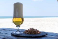 Стекло и креветки пива на каменной плите в таблице тени против солнечного пляжа запачкали предпосылку моря Стоковая Фотография