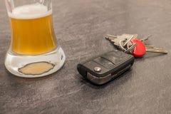 Стекло ключа пива и автомобиля на серой таблице Стоковые Изображения