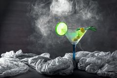 Стекло коктеиля на таблице Оливки, розмариновое масло и известка в g Стоковое Изображение RF
