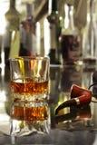 Стекло коньяка, рябиновки или whiscy на таблице зеркала бутылки в баре на предпосылке Стоковые Фотографии RF