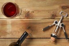 Стекло красного вина, пробочки винта и бутылки на деревянном столе стоковая фотография rf