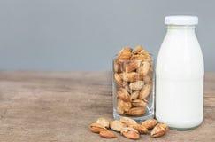 Стекло миндалин и бутылки молока на деревянном столе Стоковая Фотография