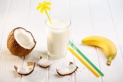 Стекло молока кокоса на белом деревянном столе, бананах тропическо стоковое изображение