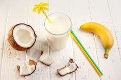 Стекло молока кокоса на белом деревянном столе, бананах тропическо стоковое фото