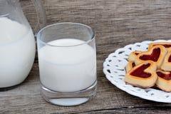 Стекло молока с печеньями сердца в плите на таблице стоковые фотографии rf