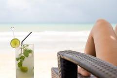 Стекло ног питья и женщины mojito на пляже Стоковая Фотография