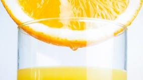 Стекло оранжевой половины изображения макроса заполняя с свежим соком Стоковое Фото