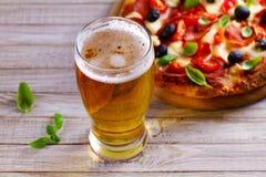 Стекло пива и пиццы на деревянном столе Концепция пива и еды aleppo стоковое фото rf