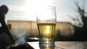 Стекло пива на заходе солнца Охлаждая концепция напитка лета Друзья и площадка для барбекю группы на предпосылке видеоматериал
