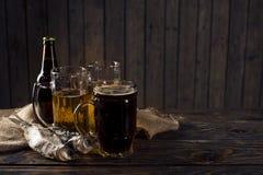 Стекло пива, посоленных рыб и гаек на деревянном столе Стоковые Изображения RF