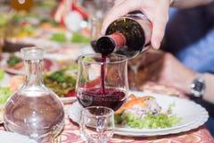 стекло полило красное вино стоковое изображение rf