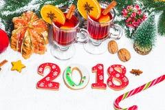 Стекло рождества красного цвета обдумывало вино на таблице с ручками циннамона, ветвями рождественской елки, снега, Стоковое фото RF