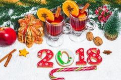 Стекло рождества красного цвета обдумывало вино на таблице с ручками циннамона, ветвями рождественской елки, снега, Стоковое Изображение