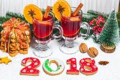 Стекло рождества красного цвета обдумывало вино на таблице с ручками циннамона, ветвями рождественской елки, снега, Стоковые Фото