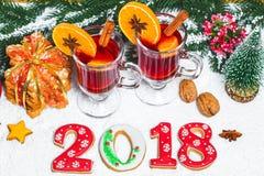 Стекло рождества красного цвета обдумывало вино на таблице с ручками циннамона, ветвями рождественской елки, снега, Стоковая Фотография RF