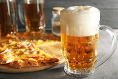 Стекло свежего пива и вкусной пиццы на таблице Стоковые Фото