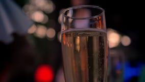 Стекло сверкная шампанского, танцуя людей на заднем плане, партия, bokeh акции видеоматериалы