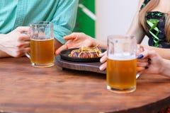 Стекло светлого пива с плитой сосиски на темной таблице в пабе Стоковое Изображение RF
