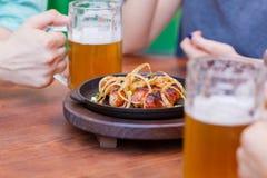 Стекло светлого пива с с плитой сосиски на темной таблице Стоковое Фото