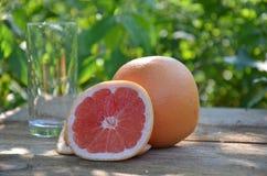 Стекло сока грейпфрута и зрелые грейпфруты на деревянной предпосылке Стоковое Фото