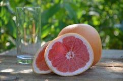 Стекло сока грейпфрута и зрелые грейпфруты на деревянной предпосылке Стоковые Фотографии RF