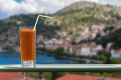 Стекло сока моркови с соломой в кафе на предпосылке городка кастории и озера Orestias Греция Стоковые Изображения RF