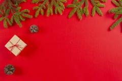 стекло состава рождества bauble голубое Ветви ели, конусы сосны и присутствующая подарочная коробка на красной предпосылке стоковое фото rf