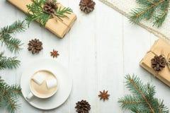 стекло состава рождества bauble голубое Подарки рождества, кофе с зефирами, конусами сосны, елевыми ветвями на деревянной белой п стоковая фотография