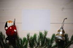 стекло состава рождества bauble голубое Подарок рождества, Санта Клаус и колокол, ветви ели на деревянной белой предпосылке, copy стоковые изображения