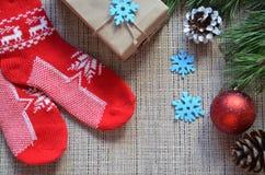 стекло состава рождества bauble голубое Подарок рождества, связанное одеяло, конусы сосны, ель разветвляет на деревянной белой пр Стоковое фото RF