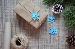 стекло состава рождества bauble голубое Подарок рождества, связанное одеяло, конусы сосны, ель разветвляет на деревянной белой пр Стоковое Фото
